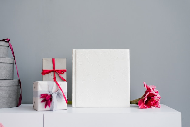 Beautiful wedding photo book in leather with embossed lace surrounded by gift boxes
