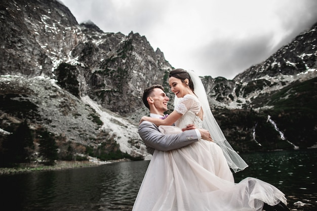 Beautiful wedding photosession, the groom circles his young bride, on the shore of the lake morskie oko, poland