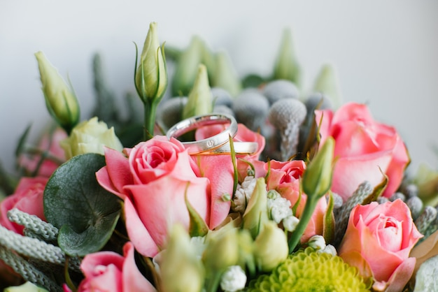 Beautiful wedding rings lie on flowers, close-up. wedding details