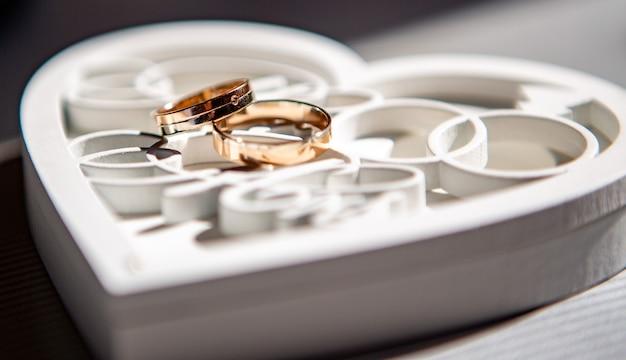 Красивые обручальные кольца лежат на деревянной белой декоративной коробке