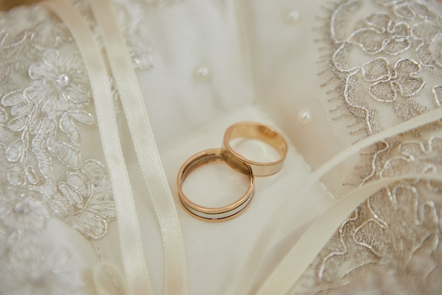 Красивые обручальные кольца лежат на фате невесты