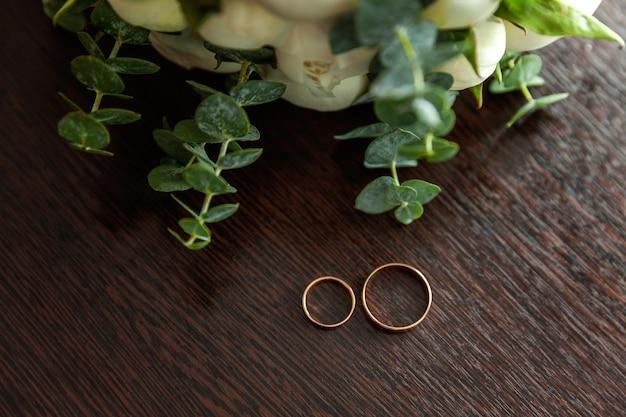 아름 다운 결혼 반지는 꽃의 꽃다발의 배경에 대해 나무 표면에 거짓말.