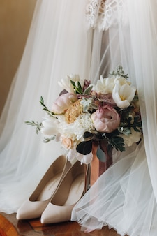 Beautiful wedding shoes, dress and flower bouquet