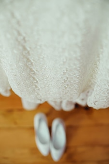 Beautiful wedding shoes and dress on a wooden brown floor