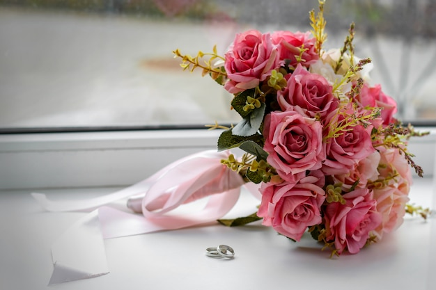 Beautiful wedding still life with a bouquet and rings