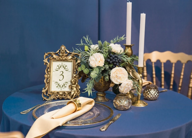 Beautiful wedding table setting and wedding decor with cutlery in gold and dark blue tones