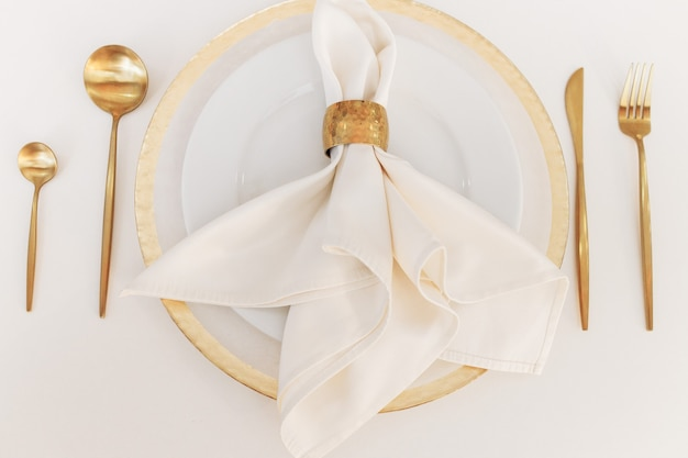 Beautiful wedding tableware lies on a white table. gold spoons and forks.