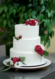 Beautiful wedding white cake with red flowers