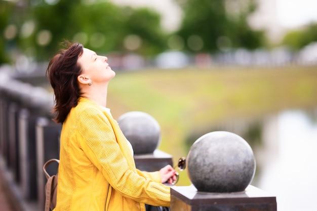 Красивая ухоженная энергичная женщина средних лет кокетливо позирует на солнышке во время прогулки Premium Фотографии