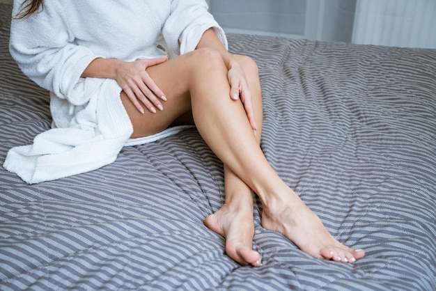 Beautiful well-groomed feet on the bed. foot skin care concept at home