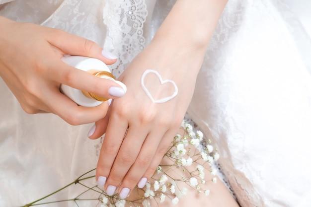 손바닥에 하트 모양의 크림이 있는 단정한 아름다운 여성의 손. 겨울철 깨끗하고 부드러운 피부를 위한 수분 크림. 하트 모양은 크림으로 만들어졌습니다. 나는 몸을 사랑한다. 건강 관리 개념입니다.