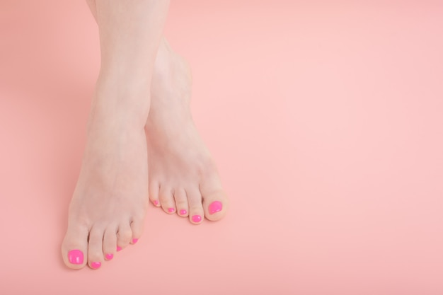 Beautiful well groomed female legs with bright pedicure on a pink background, copy space