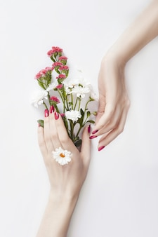 Beautiful well-groomed hands wild flowers on table