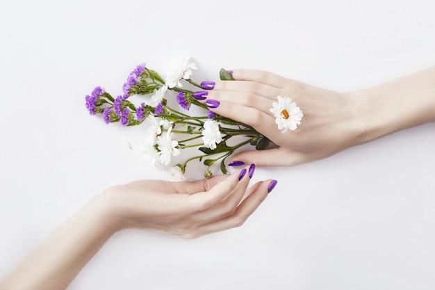 Красивые ухоженные руки с полевыми цветами на столе, косметика для рук против старения и морщин. уход за кожей и красота, увлажнение кожи и спа