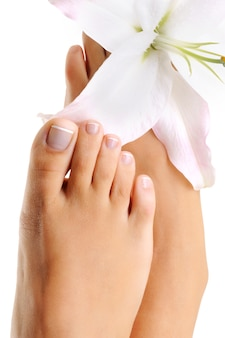 Beautiful wellgroomed female foot with the french pedicure and lily flower on it