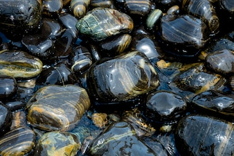 Beautiful wet black stones at Koh Hin Ngam in summer time concept travel, holiday.