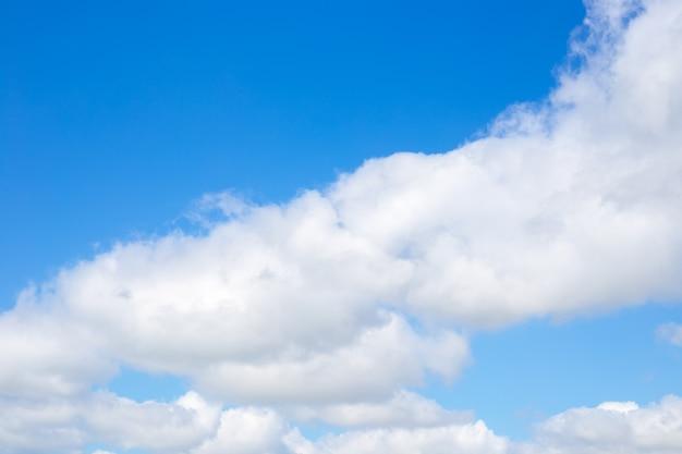 青い空を背景に美しい白い空気が浮かぶ雲。自然光の背景、テキストの場所。