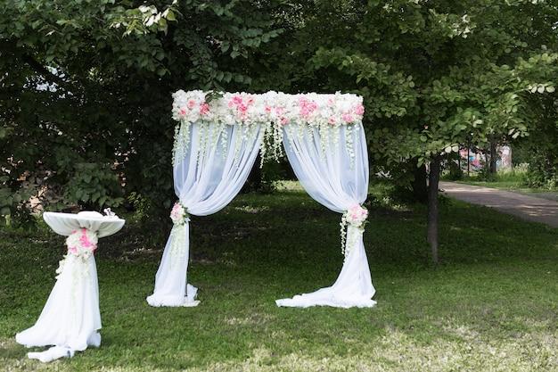 木々と緑の背景にゲストのための椅子と結婚式のための花の装飾と美しい白いアーチ