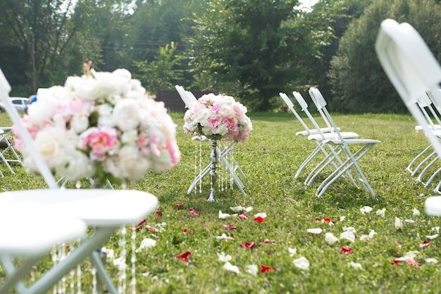 Красивая белая арка с цветочными украшениями для свадебной церемонии со стульями для гостей на зеленом фоне с деревьями
