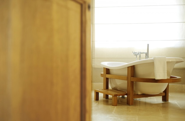 Beautiful white bath for an open door. bath stands in a wooden f