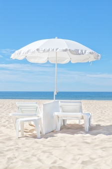 Красивый белый пляжный зонтик на солнечном пляже. что касается прочего.