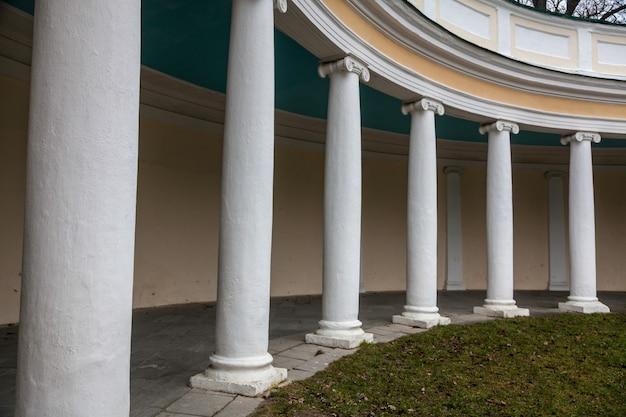 Beautiful white colonnade at autumn park