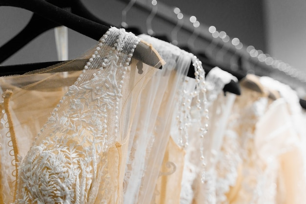 Beautiful white cream bridal dress on hangers in wedding salon. pearls and crystals pendants on the sleeves of a wedding dress.