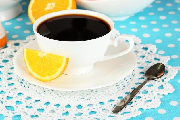 青いテーブルクロスにオレンジを使った美しい白いディナーサービス