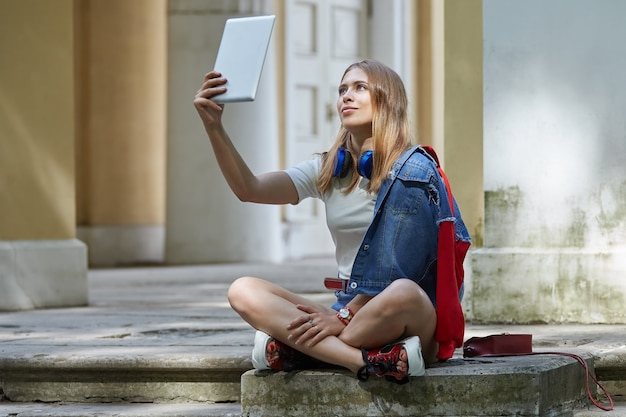 Beautiful white female blogger 20 years old in shorts is using her tablet pc while sitting on stairs.