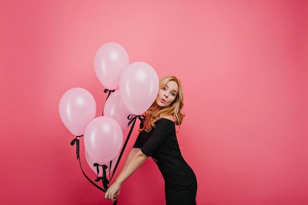 イベントで踊る美しい白人女性モデル。ピンクの風船の束を持つ楽しい白人の巻き毛の女性。