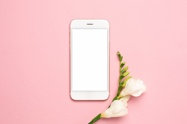 Beautiful white flower and mobile phone on pink background
