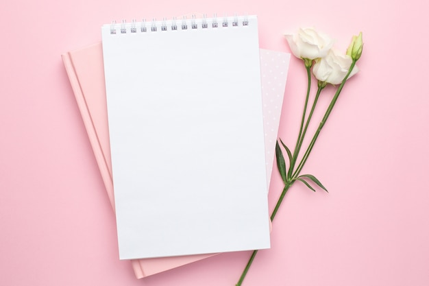 Beautiful white flower and notebook on pink