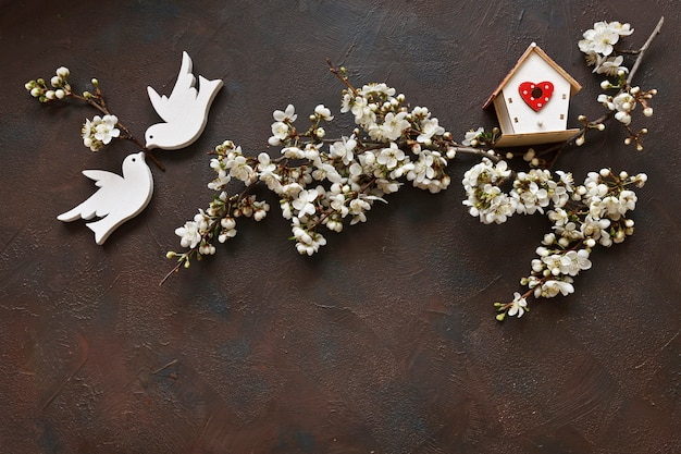 Beautiful white flowering cherry tree branches with two wooden birds and birdhouse.