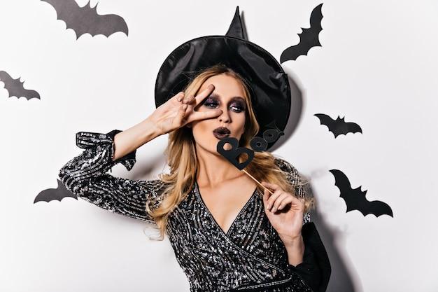Красивая белая девушка празднует хеллоуин. веселая кавказская дама веселится на карнавале.