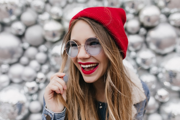 Красивая белая девушка смеется и играет со светлыми волосами на блестящей стене. фото милой женской модели в модной красной шляпе, выражающей счастливые эмоции.