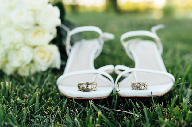 Beautiful white gold wedding rings lie on bridal shoes