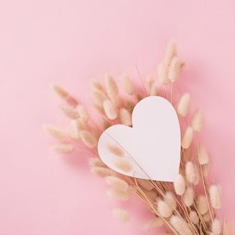 파스텔 배경에 부드러운 마른 식물이 있는 아름다운 흰색 심장