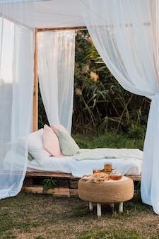 自然の中で大きなベッドと枕のある美しい白い小屋