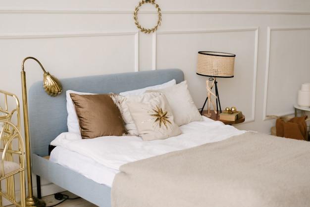 Красивый белый интерьер. классическая комната светлых стен с лепниной, кровать с подушками, украшенная декором, выборочная фокусировка