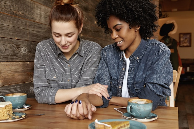トレンディなデニムジャケットで彼女のファッショナブルな黒のガールフレンドに話している髪のお団子と美しい白いレズビアン