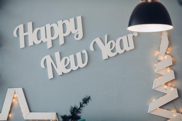 Belle lettere bianche felice anno nuovo alla parete blu in studio di decorazione moderna. accoglienti interni natalizi in un'accogliente sala di design circondata dalla luce di una lampada vintage decorativa