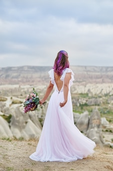 Beautiful white long dress on the woman body. perfect bride with pink hair dance. woman with a beautiful bouquet of flowers in her hands dance on the mountain in the rays of the dawn sunset