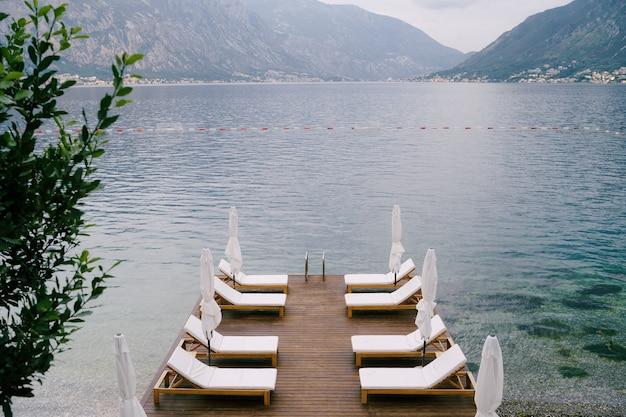 Красивые белые шезлонги и пляжные зонтики на пристани в которском заливе, черногория