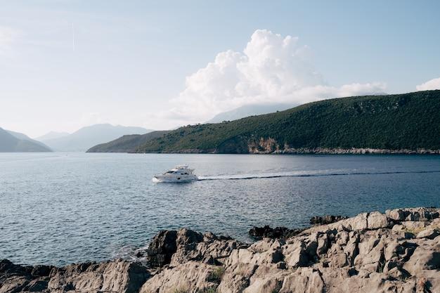 緑の山々を背景に海湾を航行する美しい白いモーターヨット