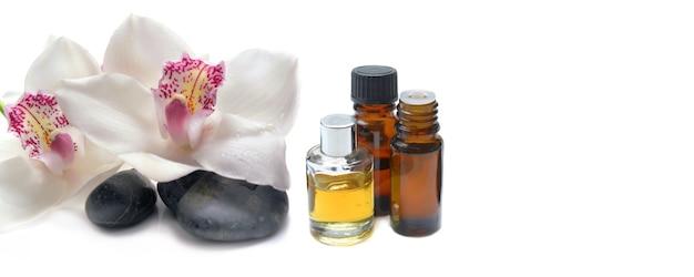 Красивая белая орхидея на гальке рядом с бутылкой эфирного масла на белом фоне