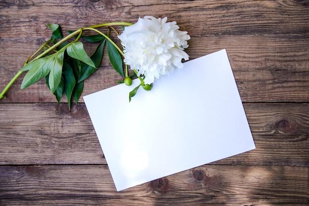 Красивый белый пион и лист бумаги на деревянном