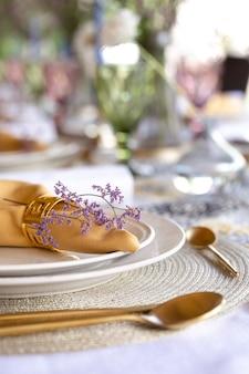 Красивая белая тарелка и бронзовые столовые приборы крупным планом
