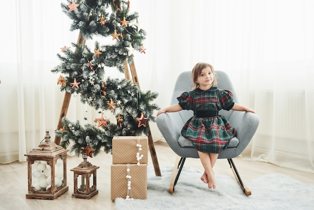 Beautiful white room. christmas and holidays conception. cute little girl is sits on the chair near ladder decorated with stars and gift boxes on the floor