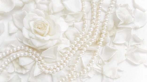 Красивая белая роза и жемчужное ожерелье на фоне лепестков. идеально подходит для поздравительных открыток на свадьбу, день рождения, день святого валентина, день матери.