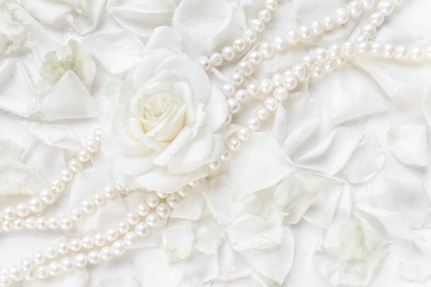 Красивые белые розы и жемчужное колье на фоне лепестков идеально подходят для поздравительных открыток.